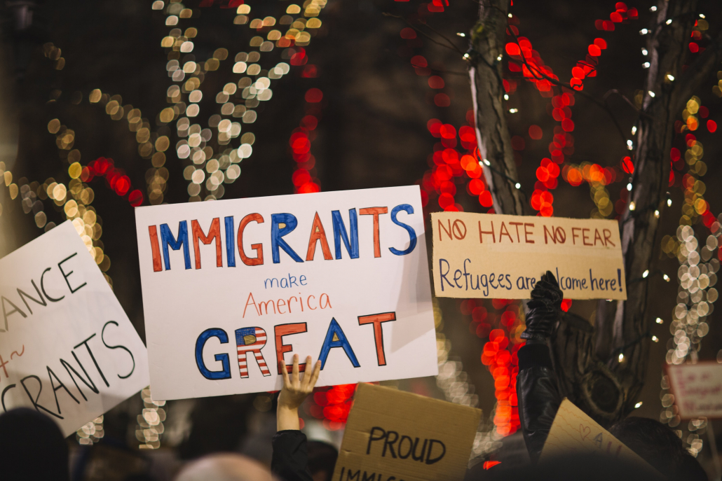 """Signs that are held up, the central one reading, """"Immigrants make America great."""""""