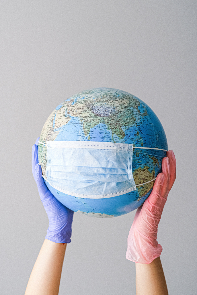 Gloved hands holding globe with mask on it