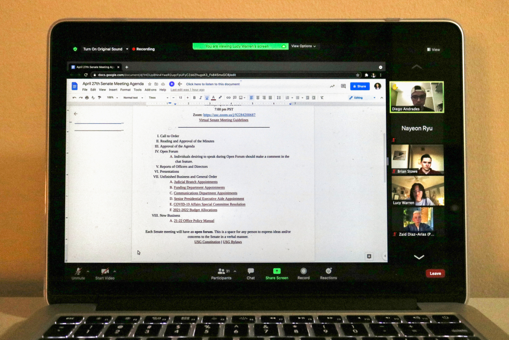 Laptop screen open to USG meeting held on Zoom. The screen shows the meeting's agenda.
