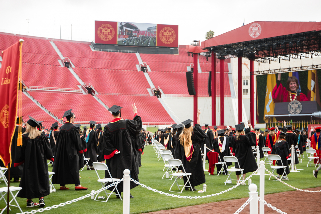 Graduates put up their Vʻs for victory with President Carol Folt at an in-person commencement ceremony.