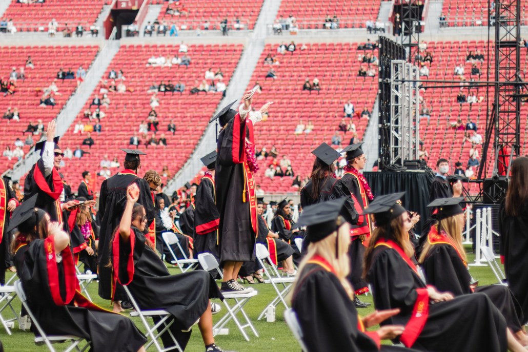 Graduates celebrate at an in-person commencement ceremony. One graduate stands on their chair with their arms extended.