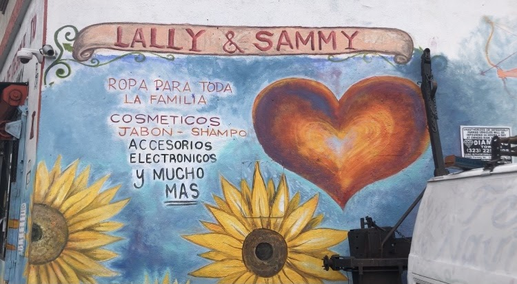 """The mural outside of Lally & Sammy's, which depicts """"Lally & Sammy"""" painted across the top, yellow sunflowers and a red heart on a blue background."""
