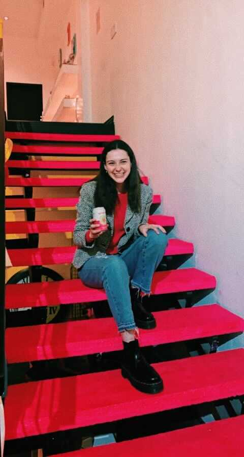 Alex Zarchy sits on a set of red stairs.