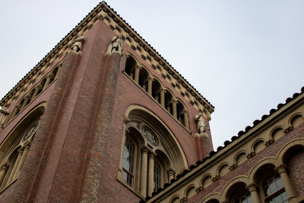 A low angle image of one of Bovard Auditorium's red bricked towers. A light grey-blue sky is displayed in the background.