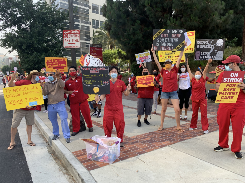 """An image of Keck nurses dressed in red holding up signs that say things like, """"if nurses are outside something's wrong inside"""" and """"on strike for safe patient care."""""""
