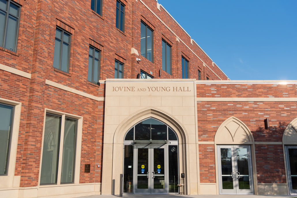 """Picture of red, brown and light grey bricked building with various beige colored window arches. Above the main entrance arch, text reads """"Iovine and Young Hall."""""""