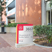 """Photo of a red and grey sign that reads """"Department of Public Safety."""" Greenery and a red brick building connected to a windowed room surround the sign."""