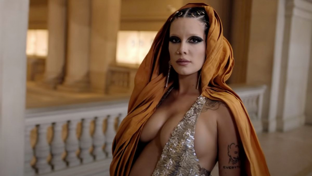 Halsey wears a tunic and sequin dress while gazing at the camera. She stands in the MET Museum.