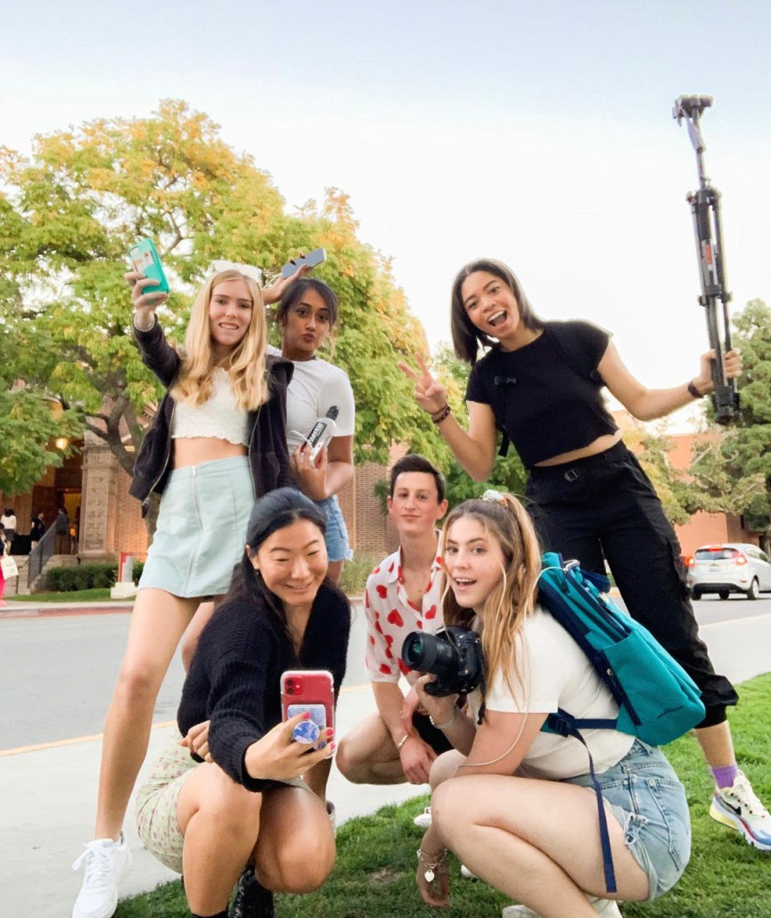 Image of six college students in front of a building. There are three students kneeling in the front, one is taking a selfie, one is posing, and another is holding a camera. In the back there are three students two are holding phones and one is holding a tripod.