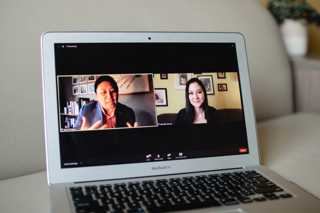 Image of a laptop with a Zoom webinar. There are two people on the screen.