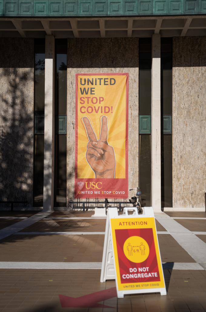 """Exterior of a building with a banner that reads """"United We Stop COVID!"""""""
