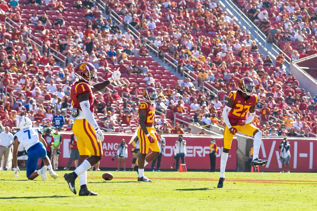 USC football players celebrate after successfully completing a pass.