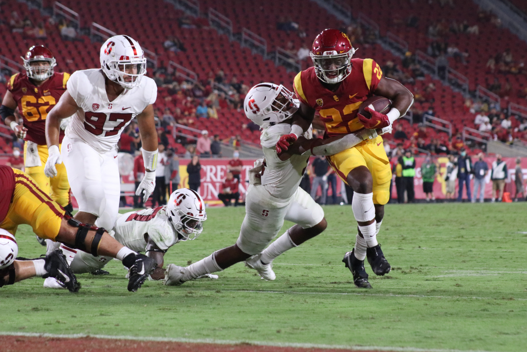 USC football running back Darwin Barlow runs toward the end zone with the ball and a Stanford defender clinging on his hip.