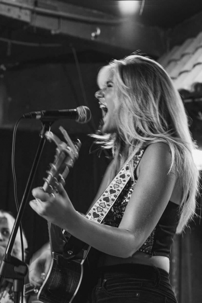 Black and white image of a woman singing into a microphone with a guitar.