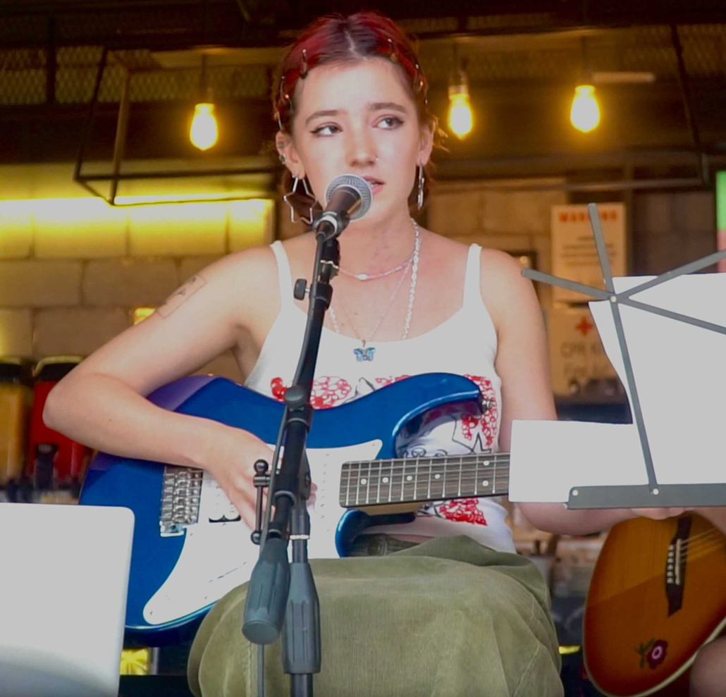 Image of Katya Urban with a blue guitar in front of a microphone.