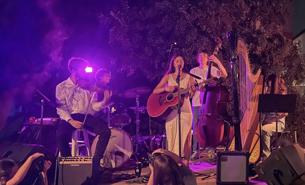 Photo of a woman with a guitar, a man with a violin, a man playing the drums, a man playing the cello, and a person playing the harp.