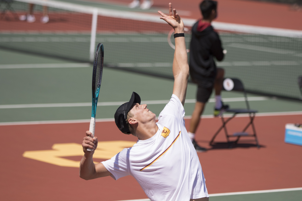 Sophomore Sean Holt tosses a ball in the air, looking to serve with his racket.
