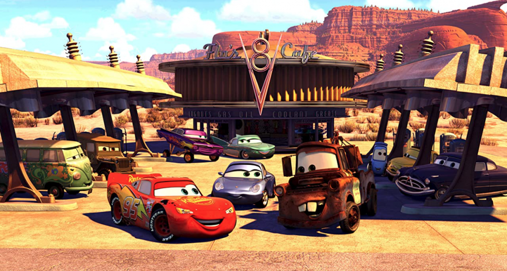 Image still from the Pixar film Cars. Features several animated cars at a gas station in front of a building with a sign that says Flo's Cafe.