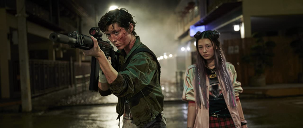 Two people, the one in front is holding a gun. The one in the back has black and purple hair and is standing behind looking at something behind the camera.