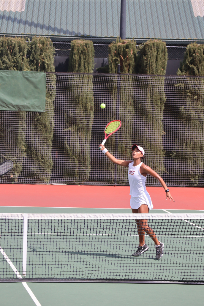 Senior Salma Ewing swings at the ball with her tennis racket in her right hand.
