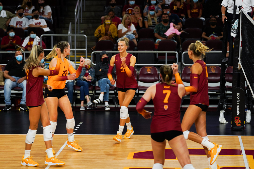 USC women's volleyball players celebrate together during a game.