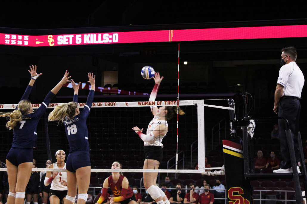 USC outside hitter Brooke Botkin attempt a spike while two defenders get ready to block it away.