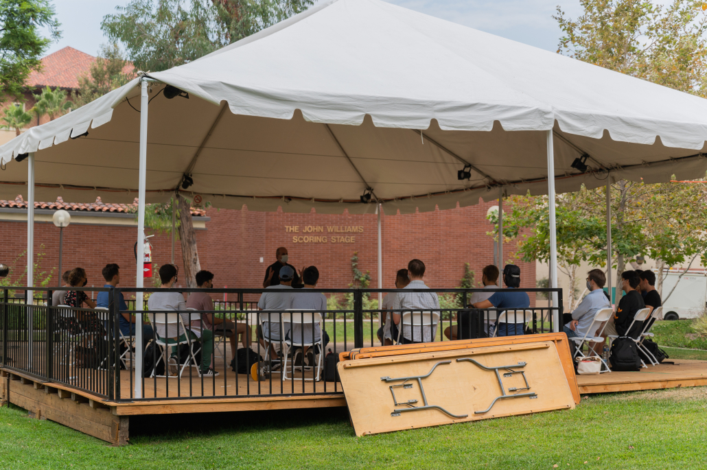 Thornton School of Music students sit at a temporary outdoor performance stage in Queens Court.
