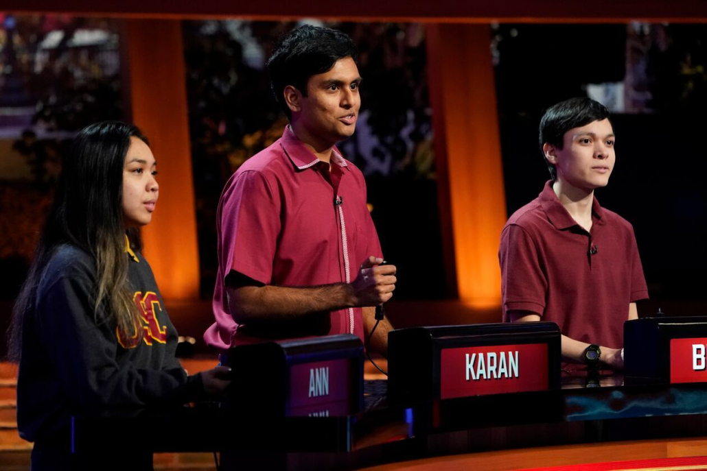 Karan Menon, Ann Nguyen and Brendan Glascock stand behind a desk on the NBC College Bowl set. Menon holds a buzzer.