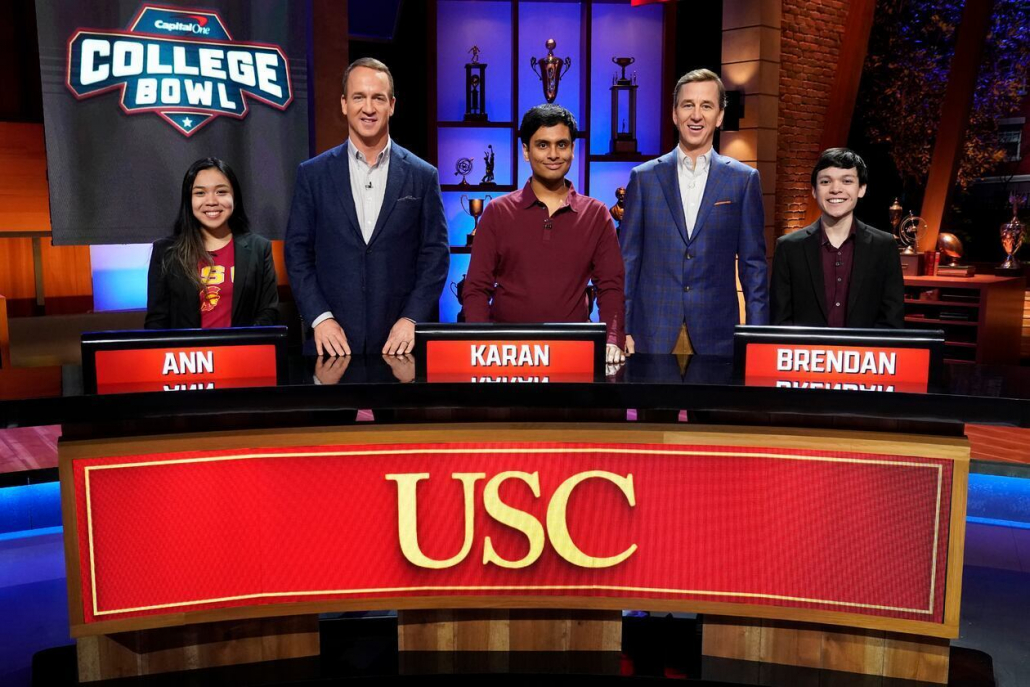 The USC Quiz Bowl team stands behind their desk on the NBC College Bowl set with Peyton and Cooper Manning. The desk has their names, Ann, Karan and Brendan, as well as USC written on it.