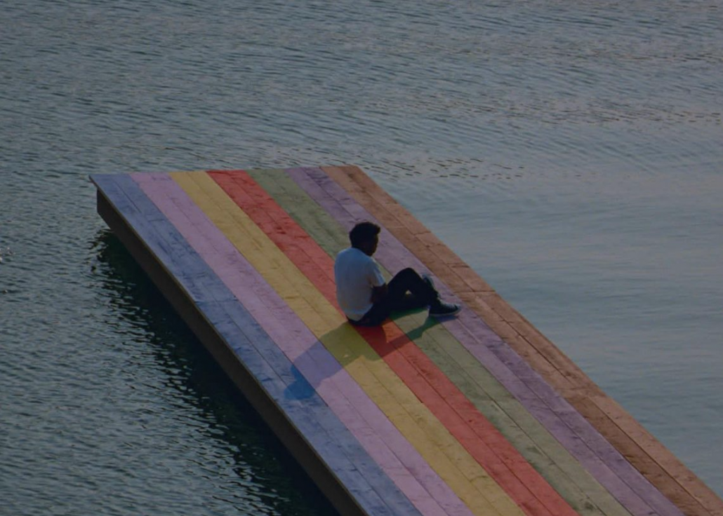 Baby Keem sits on a rainbow colored deck overlooking the water.