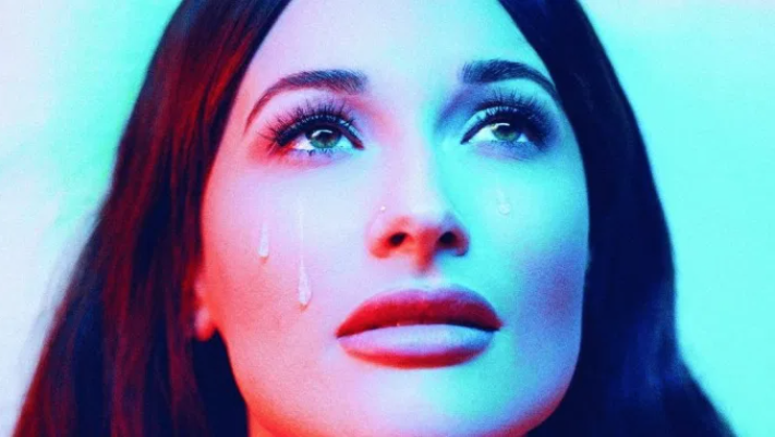 Kacey Musgraves wears teardrop makeup and stares up into glow light.