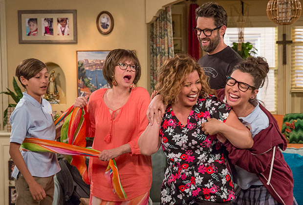 The ensemble cast of One Day at a Time frolic with each other in their living room.