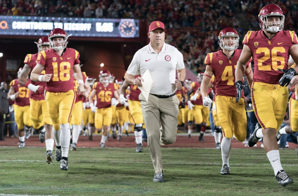Now-former head coach Clay Helton runs onto the field with his players by his side.