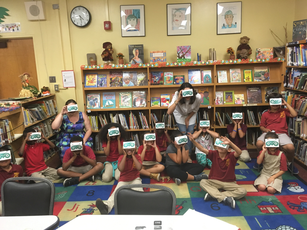 Photo of Dieuwertje Kast with students in a classroom. They are on a rug surrounded by bookcases and are holding goggles to their faces.