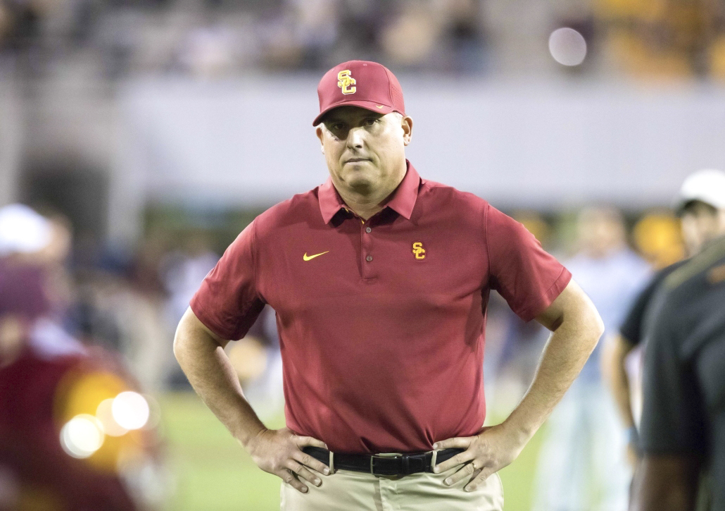 Former football head coach Clay Helton stares ahead with his hands on his hips.