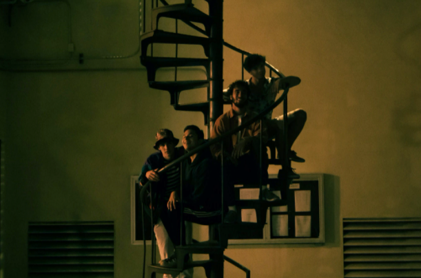 Four students sit on a winding staircase.