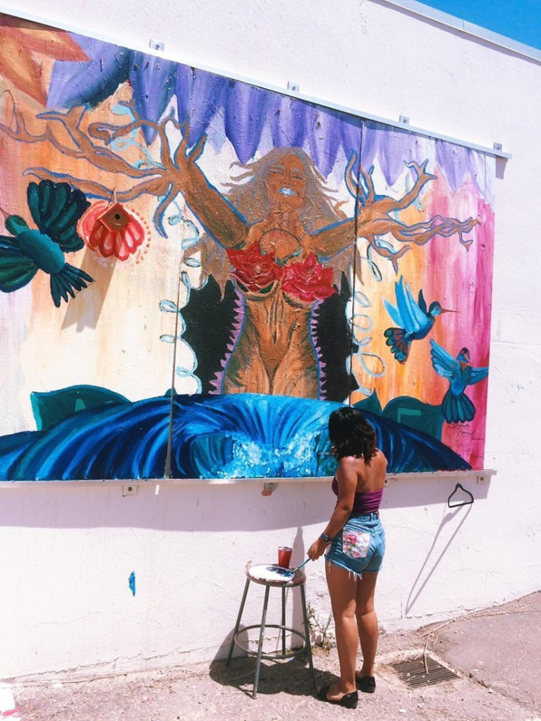 A woman paints on a large mural outside. The mural is colorful and has a picture of a woman with tree branches as hands.