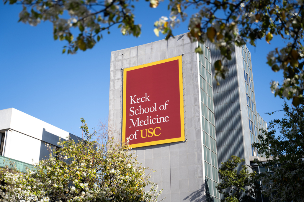 """Several storied building with a red, yellow bordered sign reading """"Keck School of Medicine of USC."""""""