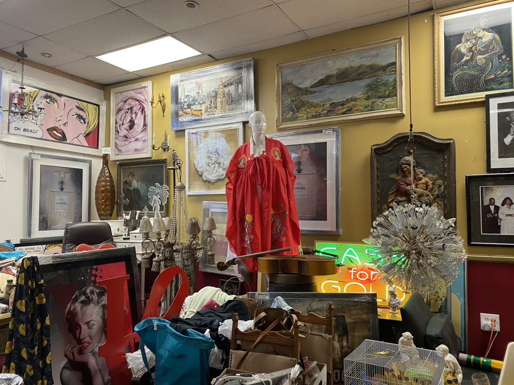 Image of the inside of an antique shop featuring colorful dresses and paintings.