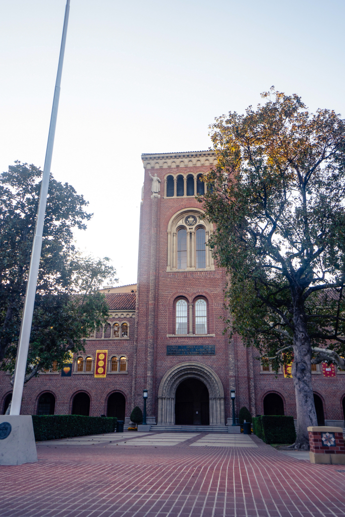 Photo of the outside of Bovard. There is a flagpole and some trees also in view.