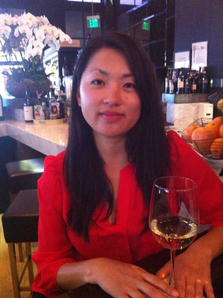 Sara Yim is sitting in a red top in a restaurant with a drink in front of her.