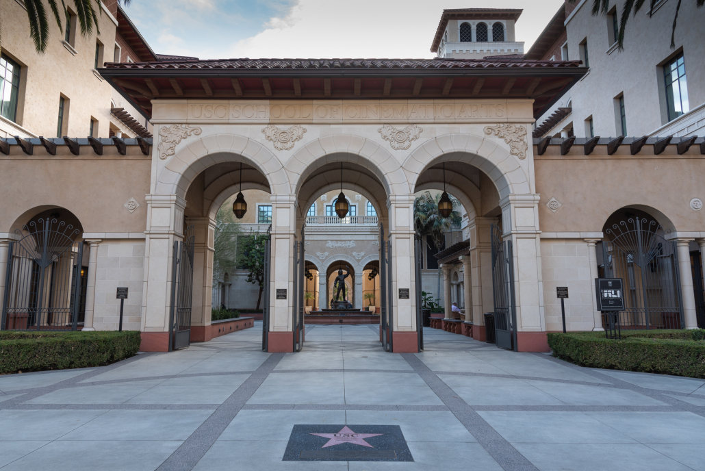 Photo of the School of Cinematic Arts, with huge arches opening into a courtyard  with a statue and fountain.