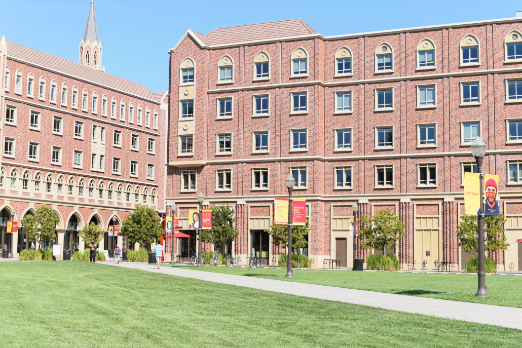Photo of the University Village housing, with red-brick buildings and a green lawn.