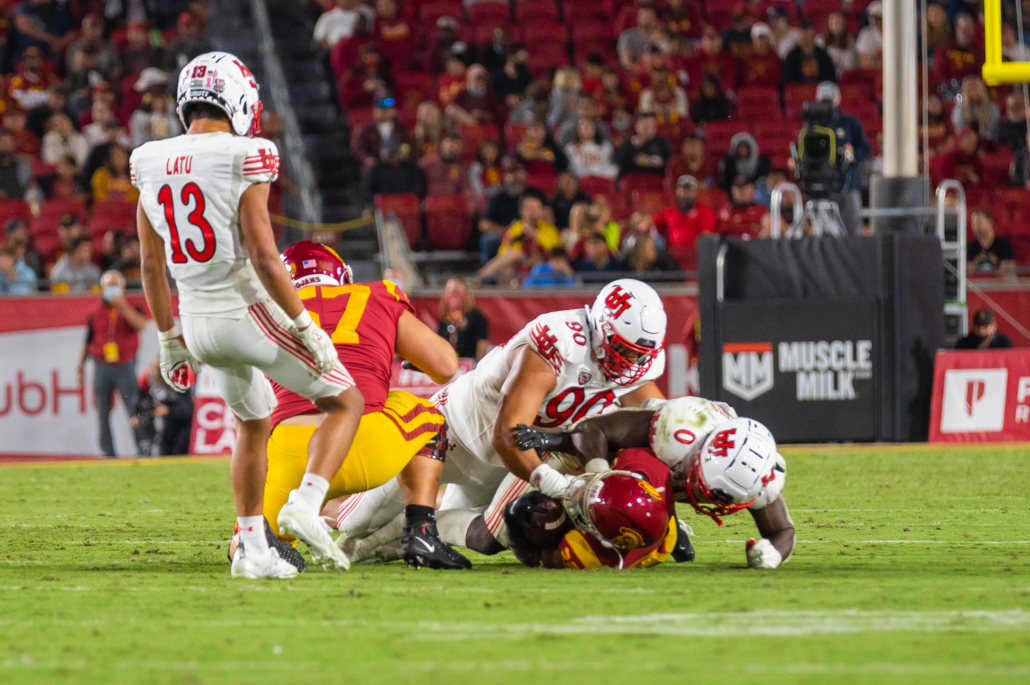 Redshirt sophomore Darwin Barlow gets tackled by two Utah players.